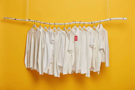 Fashionable white clothing on hangers with red tag inscriped sale, hanging on wooden rack against yellow background, copy space for your design. Black Friday discounts. New collection for females