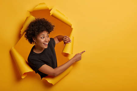 Joyous friendly looking smiling girl points aside with happy expression, toothy smile, pleased to show awesome advertisement, dressed casually says use copy space wisely gestures through ripped paper