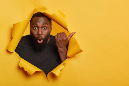 Gosh, look here. Shocked dark skinned unshaven man points thumb away, feels impressed and stunned, wears black casual t shirt, stands in torn paper hole of yellow background, has eyes popped out