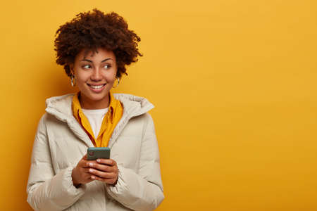Image of thoughtful young Afro American woman watches live stream online, enjoys pleasant messaging in chat, poses against yellow background in winter outerwear, looks on right side with smile