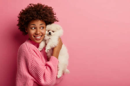 Shot of cheerful dark skinned woman embraces little lovely puppy, enjoys togetherness with dog, expresses good feelings, likes fluffy animal, looks aside, waits for friend to have walk together