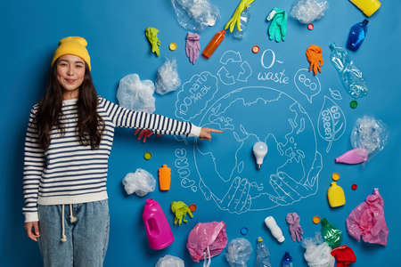 Happy Asian female volunteer prepares project about how to save Earth from pollution, demonstrates drawn planet with plastic garbage around, being ecologically aware, wears yellow hat, striped jumper