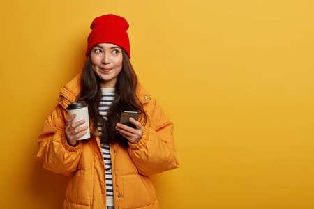 Pleasant looking Asian teenage girl messages with friends, drinks takeaway coffee, holds smartphone, looks thoughtfully aside, wears warm winter down padded coat and headgear, stands indoor.