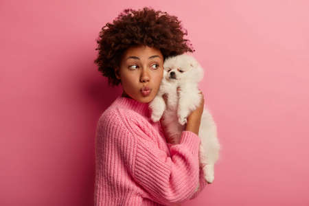 Lovely ethnic woman holds white miniature puppy closely to face, keeps lips rounded, dressed in knitted sweater, expreses love to and care to favourite pet, isolated over pink wall. Animals concept