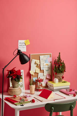 Vertical image of workplace with decorated Christmas tree, New Yeat statuette, eggnog drink in glass, different notes with future plans and motivation phrases, isolated on pink background, blank space