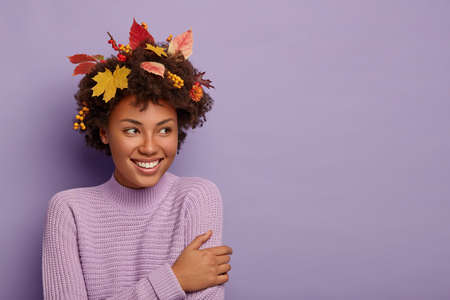Happy moments during autumn. Glad curly haired woman turns aside, has joyful gaze, being pleased by something awesome, wears casual outfit, maple leaves on head, smiles pleasantly, poses indoor