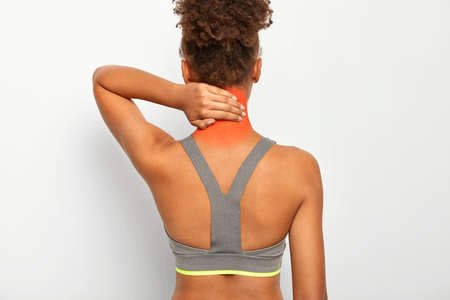 Back view of dark skinned curly woman touches neck, feels pain, needs massage, suffers from muscle injury after sport exercising, wears grey top, has incorrect sitting posture, isolated on white wall