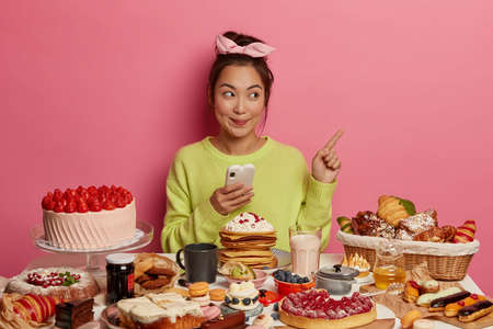 Cheerful glad brunette Asian girl surrounded by biscuits, cookies and cakes, enjoys sweet food during festive time, enjoys holidays treats, points at blank space, uses mobile phone. Cheat meal