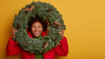 Pleased Afro teenage girl holds handmade Christmas wreath, looks away with happiness, imagines nice holiday, wears warm clothes, has broad smile, isolated over yellow wall, copy space right.