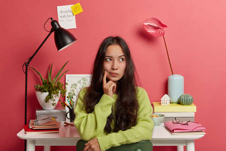 Clever thoughtful female student looks away, contemplates something, thinks about idea of making sketch for watch, prepares project, wears green sweater, poses against workplace over pink wall