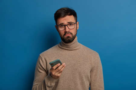 Displeased bearded guy smirks face, uses modern cellphone, cannot download application, has sad expression, wears transparent glasses and jumper, connected to wireless internet. Sad phone user