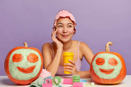 Beautiful Asian woman touches face, enjoys having soft healthy skin after taking shower, wears bathcap, drinks takeaway coffee, sits at white table with curlers, drawn faces on ripe autumn crops