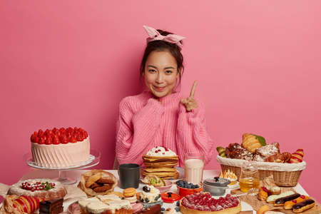 Pretty adorable woman wears headband and knitted sweater, points index finger above, being sweet tooth, enjoys unforgettable taste of dessert, surrounded with homemade cakes decorated by fresh berries