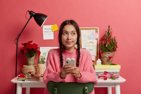 Pensive brunette teenage girl reads news message in social networks, checks balance, sits on chair against cozy desktop with decorated fir tree, eggnog, notepads, earns money online, looks aside