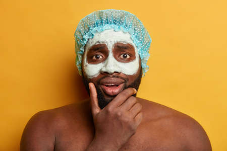 Headshot of Afro man holds chin, applies clay mud mask for having healthy skin, looks with worried expression, wears shower cap, has bare shoulders, models against yellow background. Skincare routine 版權商用圖片