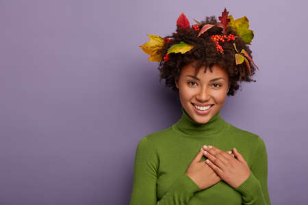 Adorable young Afro American lady feels gratitude, has hands folded on chest, weras long sleeved green jumper, leaves on curly hair, feels great and enjoys day, says thank you for compliment 版權商用圖片