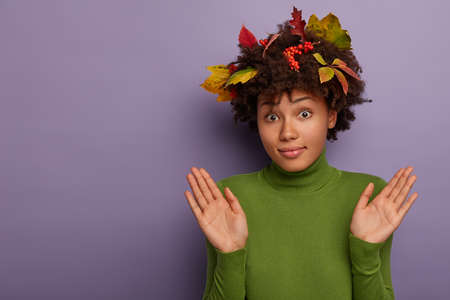 Confused curly female raises palms, shows being uninvolved, gestures in studio, has clueless face expression, says I am not guilty, wears colorful fallen autumn leaves and rowan berries in hairstyle 写真素材