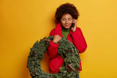 Portrait of happy pleased curly African American woman carries Christmas wreath, enjoys speaking with boyfriend via cellphone, wears red jacket, stands with eyes shut against yellow background
