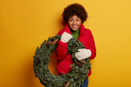 Joyful woman holds Christmas wreath made of fresh natural spruce branches for xmas design, wears winter clothes, smiles pleasantly, celebrates holiday with family, looks with eyes full of happiness