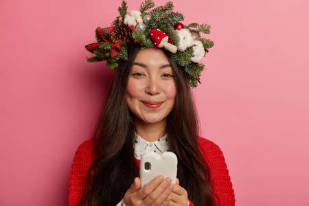 Portrait of happy brunette young Korean woman with long hair, checks newsfeed on smartphone, smiles and has dimples on cheeks, wears festive wreath, views photos on website or in social networks