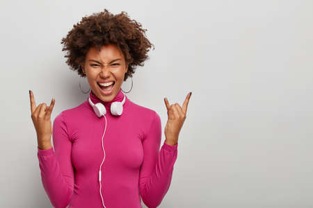 Energetic curly female meloman makes rock n roll gesture, has joyous rebellious expression, wears pink turtleneck, headphones and earrings, isolated over white background, blank space aside.