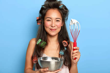 Photo of satisfied brunette woman whisks sour cream in bowl, wears hair curlers, dressed in nightdress, prepares something tasty for her family, poses against blue wall. Its time for cooking Stock fotó