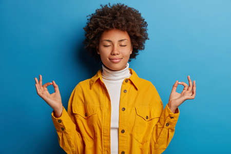 Relieved calm dark skinned woman closes eyes, makes mudra gesture, dressed in yellow shirt, feels relaxed, poses against blue background, releases stress, stands pecefully indoor in lotus pose