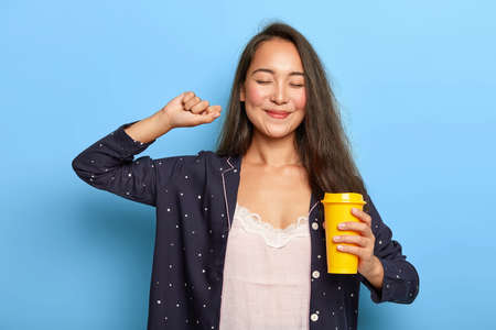 People and bedtime concept. Smiling ethnic girl stretches arms after awakening, holds takeaway coffee cup, has cheerful expression, wears no makeup, dressed in nightwear, poses indoor over blue wall Imagens
