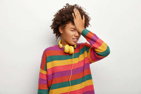 Photo of stressful ethnic woman slaps forehead with palm, forgets important information or regrets doing something wrong, wears multicolored jumper, headphones, isolated on white background.