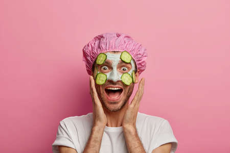 Photo of funny male model touches cheeks, laughs happily, enjoys freshness of skin, has regular beauty treatments, wears facial mask with cucumber slices, wears shower cap and t shirt, stands indoor