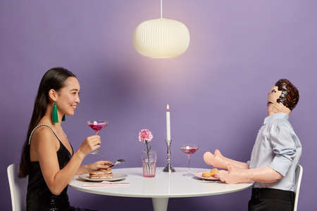 Isolated shot of happy brunette Asain woman holds glass of pink cocktail, pretends having date with gentleman, has romantic talk with inflated interlocutor, being lonely and single in real life