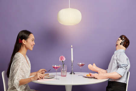 Smiling woman has pleasant talk with mannikin, imitates dating, forgets about real problems with unreal boyfriend, has unrequited love enjoys romantic dinner in cozy restaurant isolated on purple wall Foto de archivo