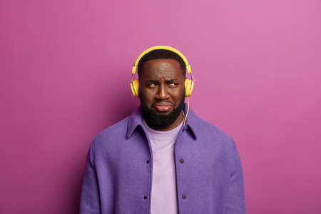 Discotent man upset as something went wrong with his headphones, cannot listen music, looks sadly aside, has gloomy face expression, wears headset, stands against lilac studio wall. Technology problem