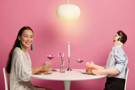 Horizontal shot of woman and inflated doll man have dinner together with candle, drink cocktail, pretend being boyfriend and girlfriend. Asian female dates with unreal layman, pose in restaurant