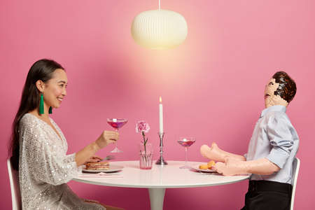 Photo of Korean woman in festive dress, holds glass of cocktail, imitates romantic date with lover in cozy restaurant, feels lonely being single hearted, has conversation with inflated mannikin Foto de archivo
