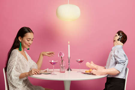 Pleased Korean woman being in love, prepares for first date with stranger, sits at round white table with layman doll, simulates relationship, have romantic dinner, isolated over rosy background Banco de Imagens