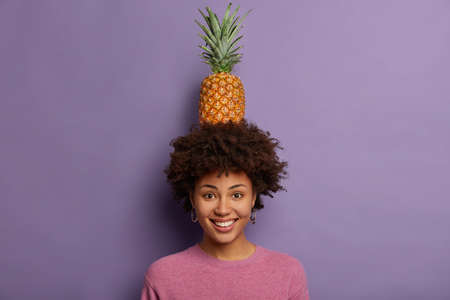 Portrait of attractive young woman plays with ripe pineapple, looks at camera, smiles broadly, shows white teeth, wears casual jumper, isolated over purple background. Look how I can, what trick