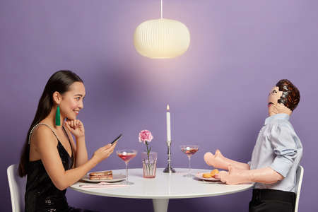 Happy young Eastern woman has online dating, prepares for real meeting with man, finds perfect match in internet, sits at festive table with inflated doll. Social media and relationship concept