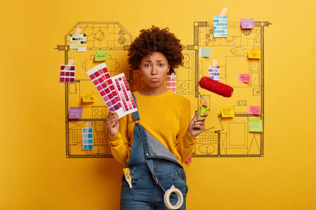 Discontent dark skinned woman smirks face and looks sadly at camera, holds color samples and paint roller, isnt eager to refurbish room walls, stands against house sketch, renovates apartment