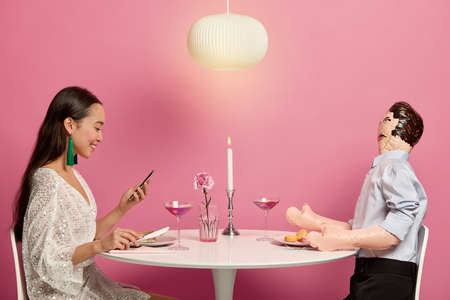 Perfect relationship dream concept. Happy good looking woman uses modern mobile phone for searching partner online, has dinner with layman doll, simulates dating, sends text messages to stranger