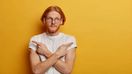 Confused youngster with red bob hair, beard, crosses arms over body and points sideways, chooses between two options, has hesitant expression, gets good suggestions selects better thing, wears glasses