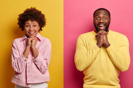 Studio shot of joyful positive ethnic male and female smile broadly, keep hands under chin, looks gladfully at camera, listen interlocutor attentively, pose tgether against two colored background