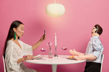 Romantic female makes video call, pouts lips for kiss as looks at smartphone camera, finds lover in social networks, dreams about romantic relationship, imitates dinner with unreal inflated man Foto de archivo