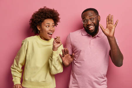 Joyful dark skinned couple dance with arms raised, have carefree lifestyle, feel optimistic and delighted, move with rhythm of pop music, isolated over pink background. Happy emotions concept Stock Photo