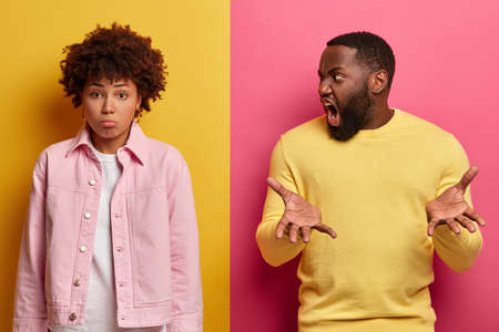 Irritated bearded man shouts angrily at girlfriend, blames of doing something wrong, raises palms, gestures actively. Sad guilty Afro American woman purses lips unhappily, sort out relationships