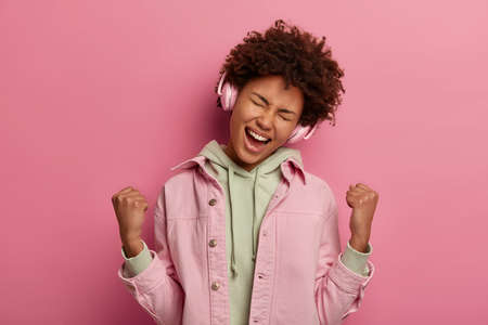 Portrait of triumphing woman clenches fists with joy, picks song that effects mood, feels like winner, celebrates winning contest wears jacket, isolated on pink wall. People, cheering, success concept