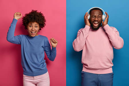 People, music, emotions concept. Overjoyed black woman and man, Afro couple dance and move actively with rhythm of music, wear stereo headphones, dressed casually, have fun during disco party Stock Photo