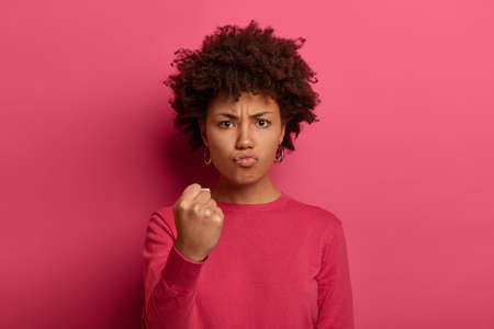 Irritated outraged young woman clenches fist, shows anger and looses temper, looks with annoyance at camera, expresses negative emotions, isolated over pink background, makes threaten gesture