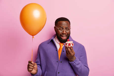 Lonely Afro man looks with dissatisfaction at small sweet cupcake, celebrates festive event alone, holds air balloon, dressed in bright elegant clothes, poses indoor. Spoiled holiday concept Archivio Fotografico