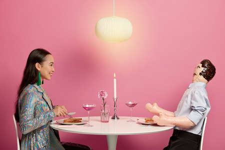 People, intimacy, relationship concept. Positive Asian woman dressed in festive clothes pretends having romantic dinner with her lover, has talk with inflated man manniquin. Love simulation.